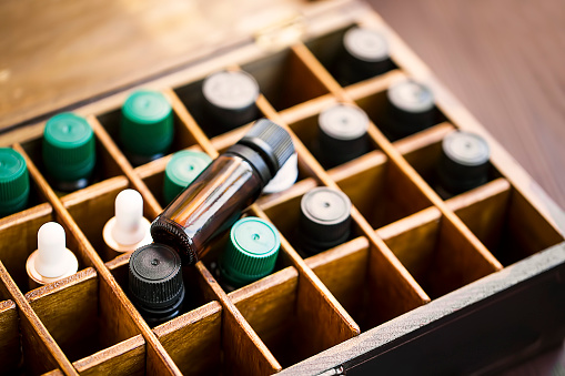 Aromatherapy essential oils in wooden box. Herbal alternative medicine with essential oils bottles in wooden box, healthy organic natural therapy 1132317868