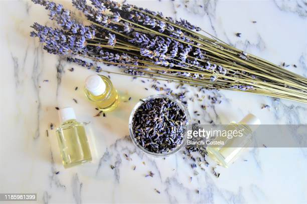 aromatic oils with lavender flowers on marble background - essential oil stock pictures, royalty-free photos & images