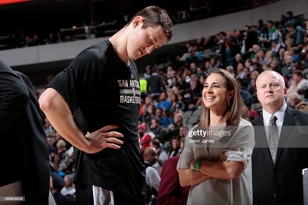 Aron Baynes #16 and Becky Hammon of the San Antonio Spurs talk before the game against the Dallas Mavericks on December 20, 2014 at the American Airlines Center in Dallas, Texas.