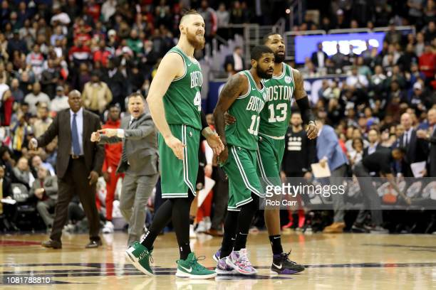 Aron Baynes Kyrie Irving and Marcus Morris of the Boston Celtics walk off the floor during a second half timeout against the Washington Wizards at...