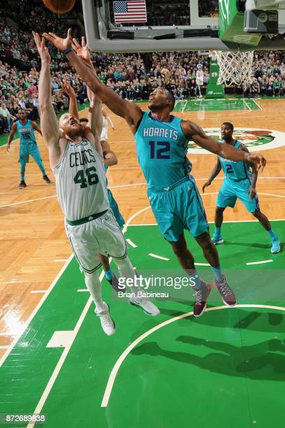 Aron Baynes of the Boston Celtics and Dwight Howard of the Charlotte Hornets jump for the rebound on November 10 2017 at the TD Garden in Boston...