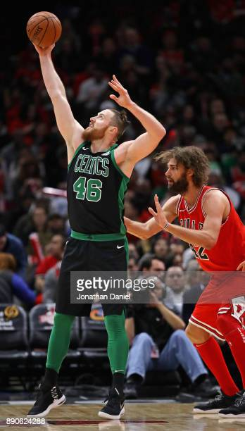 Aron Baynes of the Boston Celtics reaches for a pass as Robin Lopez of the Chicago Bulls defends at the United Center on December 11 2017 in Chicago...
