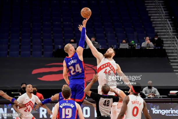 Aron Baynes of the Toronto Raptors and Mason Plumlee of the Detroit Pistons fight for the jump ball to start the game at Amalie Arena on March 03,...