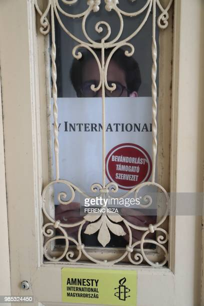Aron Demeter press officer for Amnesty International Hungary poses on June 27 2018 with a poster that was placed on the street door of Amnesty's...