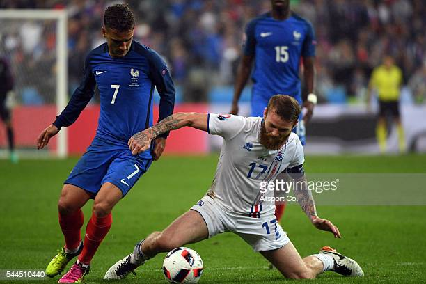 Aron Gunnarsson of Iceland battles with Antoine Griezmann of France during the UEFA EURO 2016 quarter final match between France and Iceland at Stade...