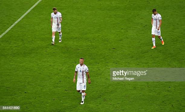 Aron Gunnarsson Ragnar Sigurdsson and Kari Arnason of Iceland look dejected during the UEFA EURO 2016 quarter final match between France and Iceland...