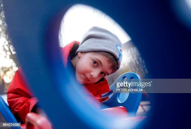 Aron looks into the camera at a local playground in Budapest on November 22 2017 Shrieks of laughter by nondisabled and disabled children having fun...