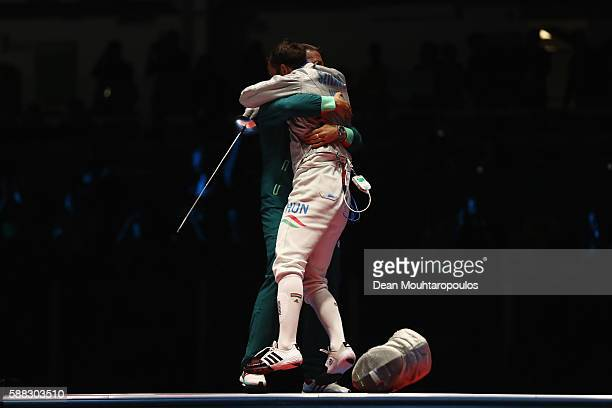 Aron Szilagyi of Hungary embraces his coach following victory against Daryl Homer of the United States in the men's individual sabre gold medal bout...