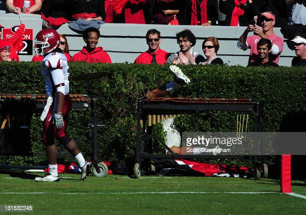 Aron White of the Georgia Bulldogs gets stuck in the hedges after scoring a touchdown against the New Mexico State Aggies at Sanford Stadium on...