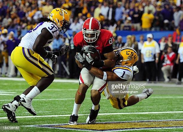 Aron White of the Georgia Bulldogs makes a catch for a touchdown against Eric Reid of the LSU Tigers during the SEC Championship Game at the Georgia...
