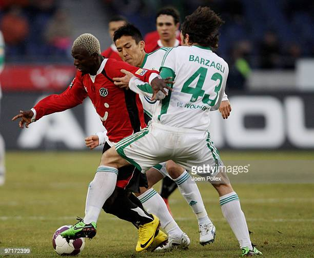 Arouna Kone of Hannover and Andrea Barzagli and Makoto Hasebe of Wolfsburg compete for the ball during the Bundesliga match between Hannover 96 and...