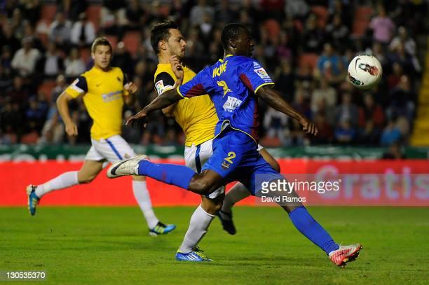 Arouna Kone of Levante UD shoots towards goal under a challenge by Alberto de la Bella of Real Sociedad during the La Liga match between Levante UD...