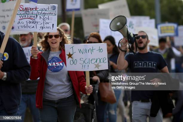 Around a hundred protesters march toward the NASA Ames Research Center to hold a rally and speak out against the government shutdown in Mountain View...