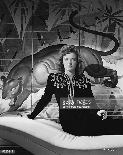 Around the time of her starring role in Jacques Tourneur's 'Cat People' French film actress Simone Simon poses in front of a screen depicting a...