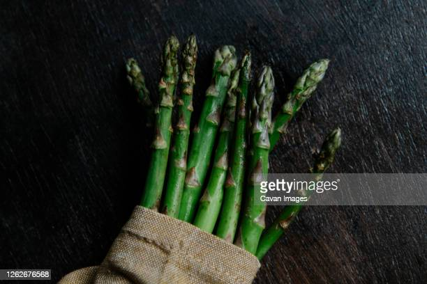 arranged green stems of asparagus wraped inside a cloth - rijp voedselbereiding stockfoto's en -beelden