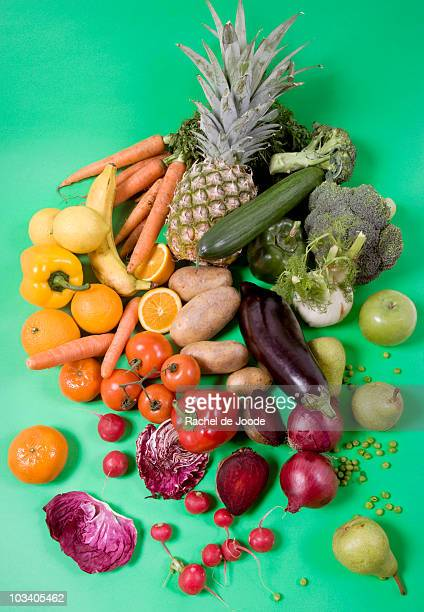 Arrangement of fruits and vegetables on a green background