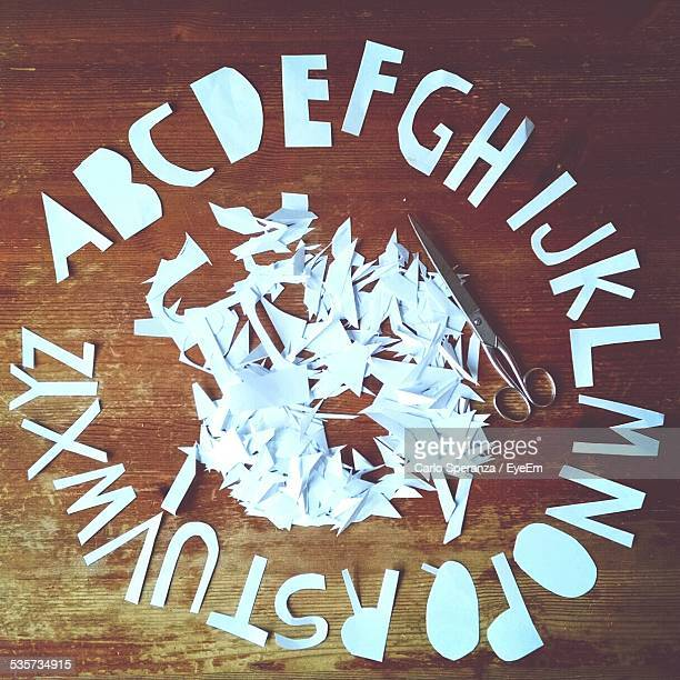 Arrangement Of Paper Cut Alphabets On Wooden Table