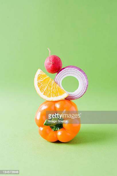 Arrangement of pepper, onion, orange and radish against green background