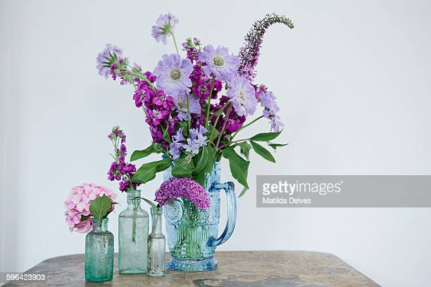 Arrangement of purple flowers in glass bottles