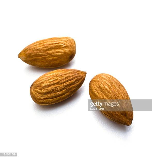 Arrangement of three almonds against white background