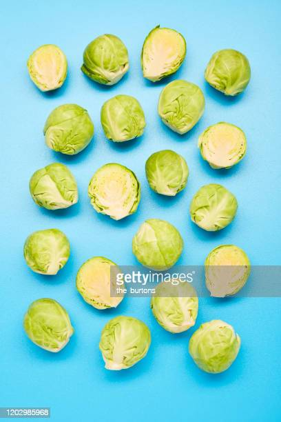 arrangement of whole and halved brussels sprouts on blue background - 芽キャベツ ストックフォトと画像