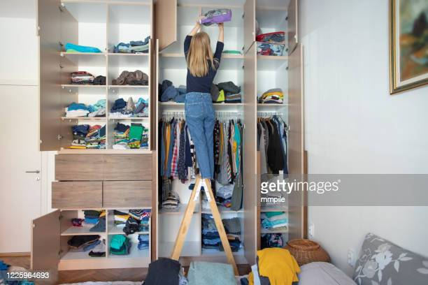 arranging wardrobe during home isolation - neat stock pictures, royalty-free photos & images