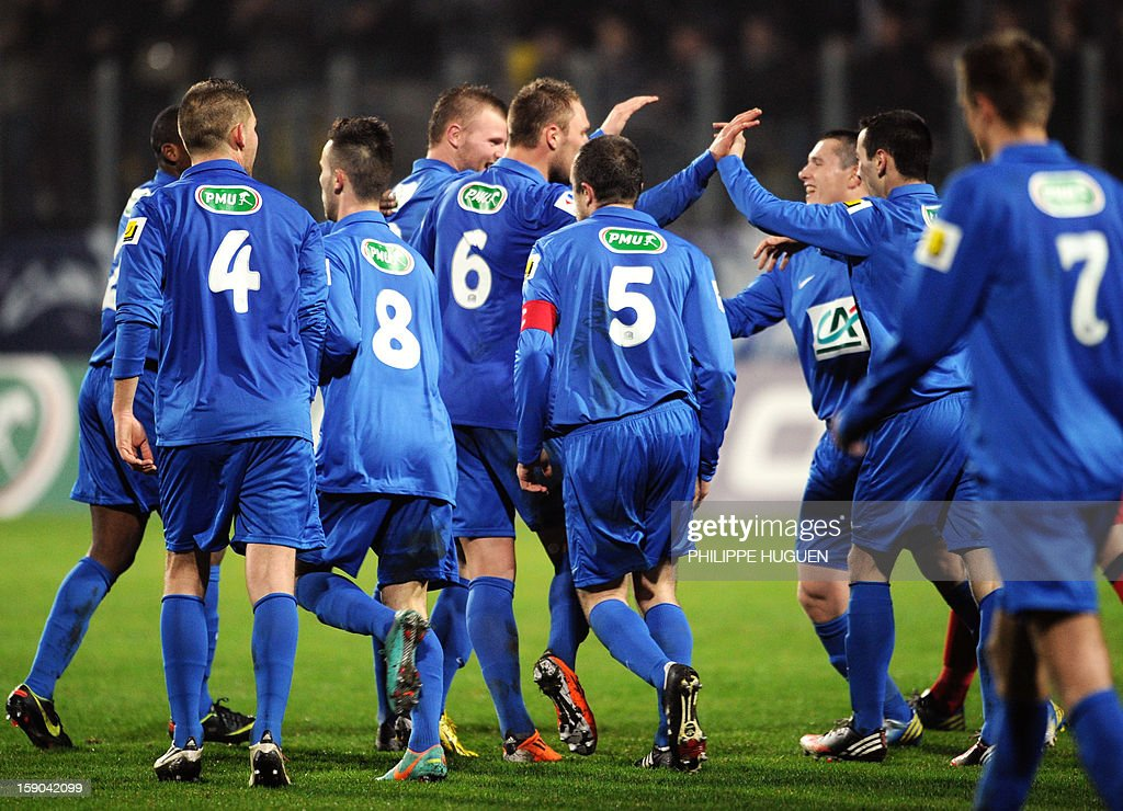 Arras' forward Despres Arnaud (C) is congratulated by his teammates after scoring a goal during the French cup football match Arras vs Paris Saint-Germain, on January 6, 2013 at the Epopee Stadium in Calais, northern France.