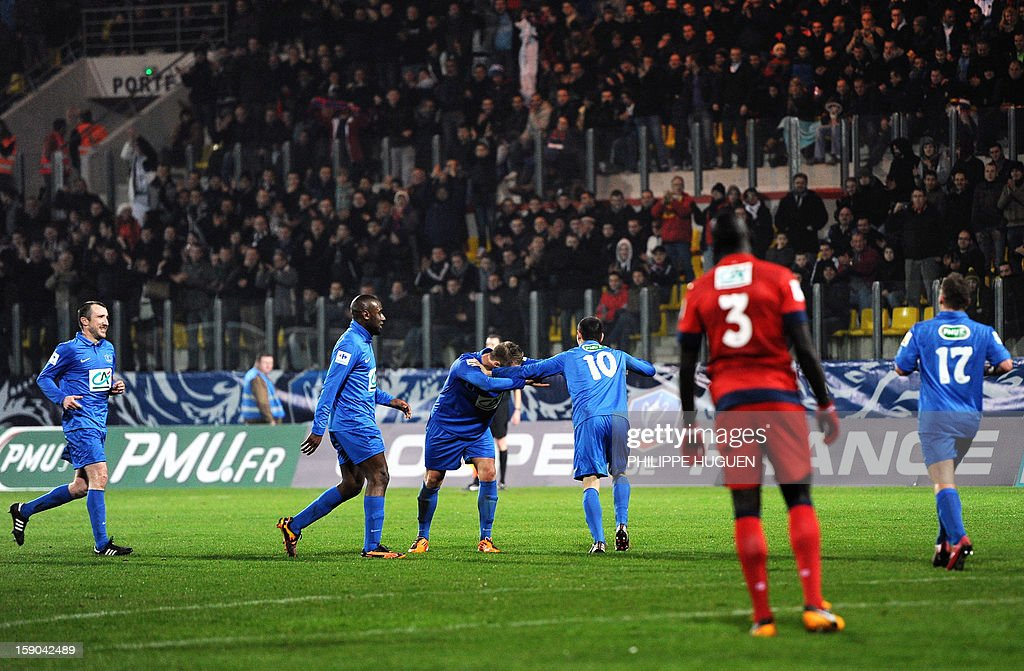 Arras' midfielder Bernard Sebastien (C) is congratulated by his teammates after scoring a goal during the French cup football match Arras vs Paris Saint-Germain, on January 6, 2013 at the Epopee Stadium in Calais, northern France.