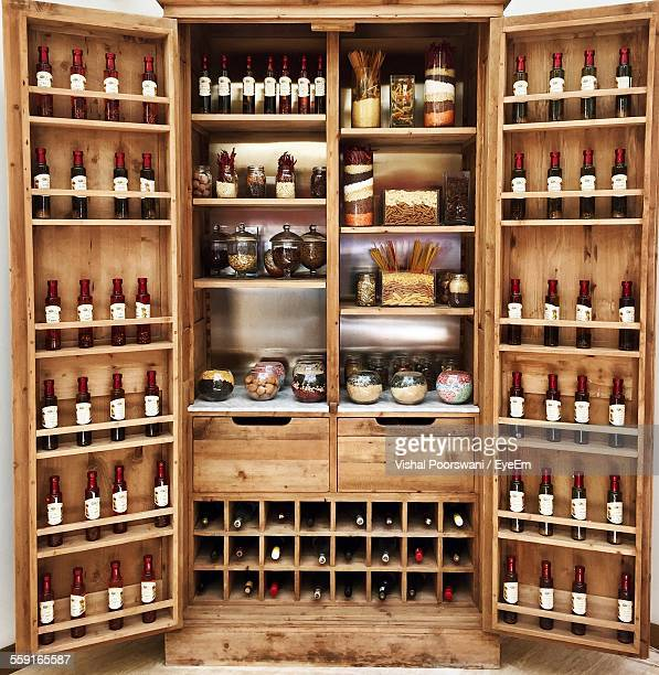 Array Of Wine Bottles And Food Stored In Wooden Shelves