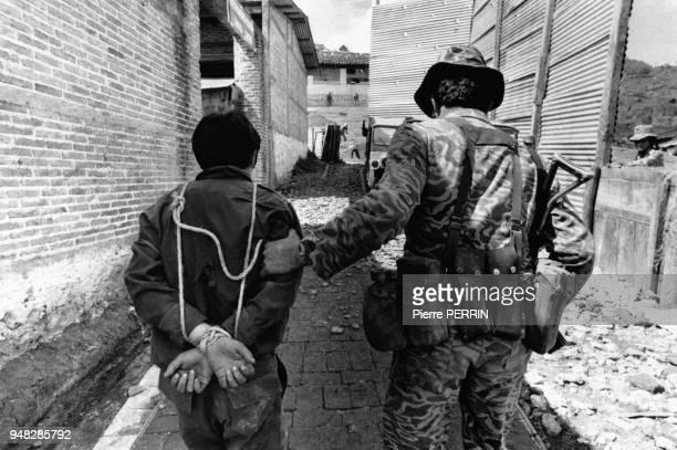 Arrestation par un militaire de l'armée d'un Nicaraguayen venu supporter la guerilla en mars 1982 au Guatemala.