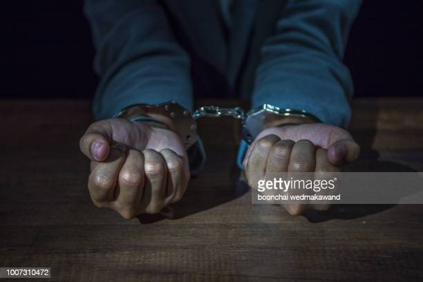 arrested business man handcuffed hands. close-up. - detenido fotografías e imágenes de stock