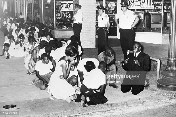 Arrested for parading without a permit a group of 500 African American demonstrators led by Rev Samuel B Wells kneel in prayer on a sidewalk in...