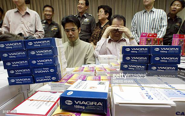Arrested Japanese nationals Hideo Aoyagi and Yuichi Nakamura sit behind their unlicenced confiscated sex medicines at the Thai immigration department...