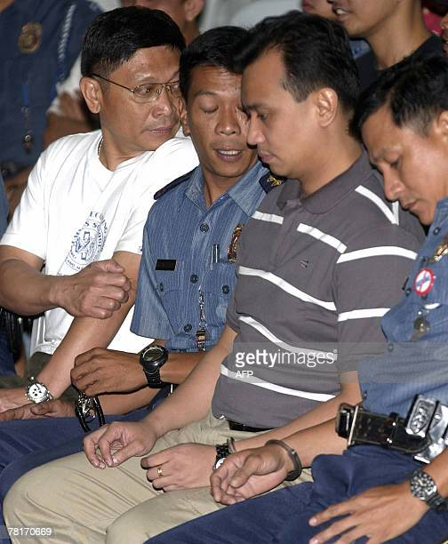 Arrested leaders of the failed mutiny Senator Antonio Trillanes and Brigadier General Danilo Lim are handcuffed to police escorts as the group face...