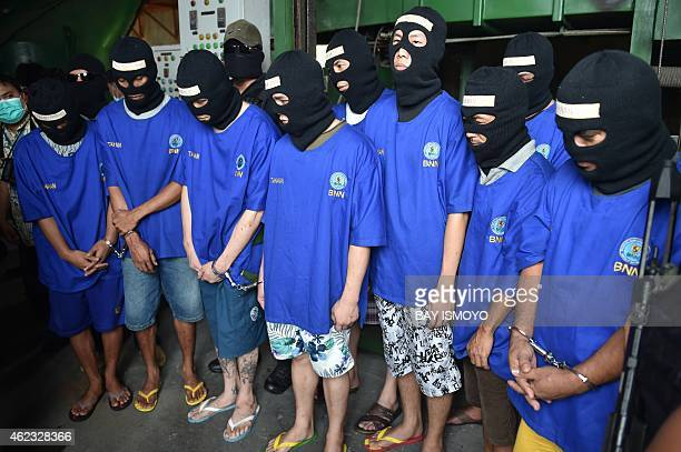 Arrested members of the international drug syndicates including major Hong Kong drug lord Wong Chi Ping wearing masks are escorted by police and...