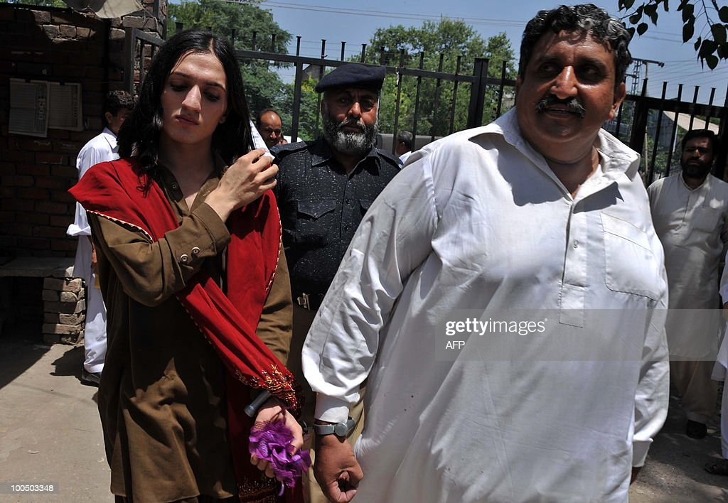 Arrested Pakistani Malik Iqbal (R) and his eunuch partner Kashif leave court in police custody in Peshawar on May 25, 2010. Police arrested Iqbal for marrying a eunuch in northwestern Pakistan. Under Pakistani law gay marriage or a man�s marriage to a eunuch is a criminal offence and carries a maximum 10-year prison sentence.