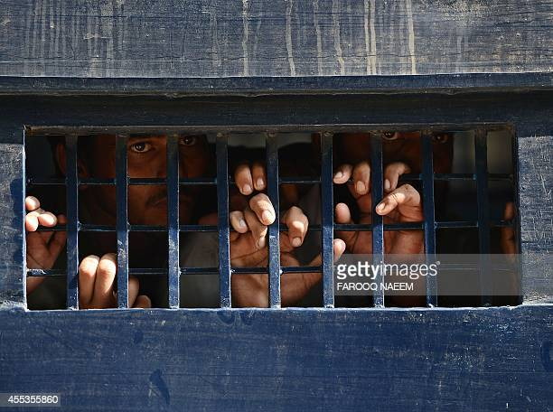 Arrested Pakistani opposition workers look out from a prison van following a protest at the court area in Islamabad on September 13 2014 A court in...