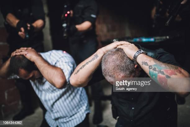 swat arresting gangster in warehouse - detenção imagens e fotografias de stock
