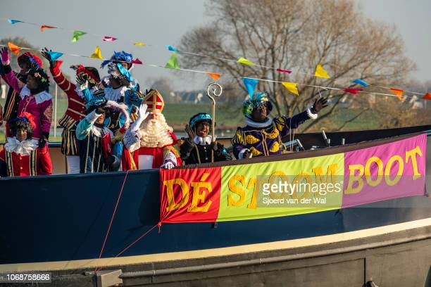 Arrival of Sinterklaas in the city of Kampen on the steam boat with Sinterklaas standing on the boat'u2019s bow surrounded by his helpers the Black...