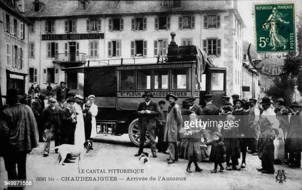 Arrivée de l'autobus automobile devant les badauds à ChaudesAigues dans le Cantal en France