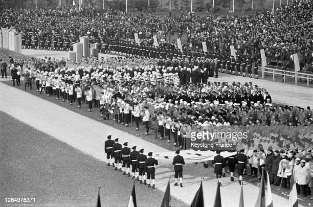 Arrivée du drapeau olympique porté par les chasseurs alpins lors de la cérémonie d'ouverture des Jeux olympiques à Grenoble, France en février 1968.