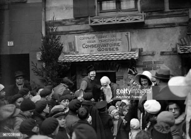 L'arrivée du Père Noël sur la place du Tertre à Montmartre entouré par les enfants à Paris France le 24 décembre 1933