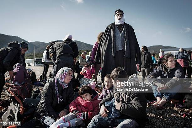 Arrived on the shores of Lesbos near Mytilene airport refugees from Afghanistan and Syria wait to be shuttled to a registration camp by bus Greece on...