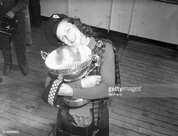 Arriving aboard the SS Queen Elizabeth in New York is Babe Didrikson Zaharias who holds the trophy she won by capturing the British Women's Amateur...
