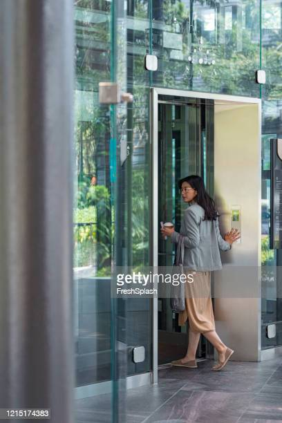 arriving at work: asian businesswoman enters an elevator in an office building - entering stock pictures, royalty-free photos & images