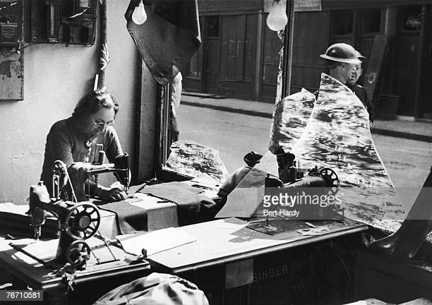 Arriving for work as usual Mrs Marsh works amongst the broken glass of a tailor's shop after an air raid on the East End of London during the Blitz...