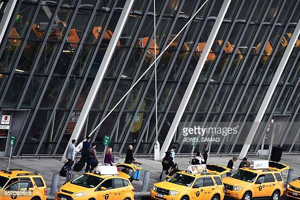 Arriving passengers line up to get taxi outside of Terminal 4 at the JFK airport in New York on October 11 2014 The airport started health screenings...