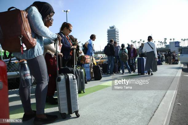 Arriving passengers wait in line to board Uber vehicles at the new 'LAXit' ridehail passenger pickup lot at Los Angeles International Airport on...