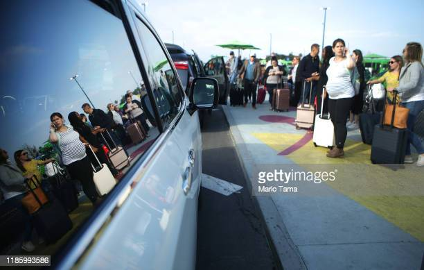 Arriving passengers wait to board Uber vehicles at the new 'LAXit' ridehail passenger pickup lot at Los Angeles International Airport on November 6...