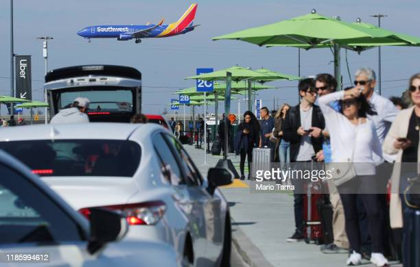 Arriving passengers wait to board Uber vehicles at the new 'LAXit' ridehail passenger pickup lot as a Southwest Airlines plane lands at Los Angeles...